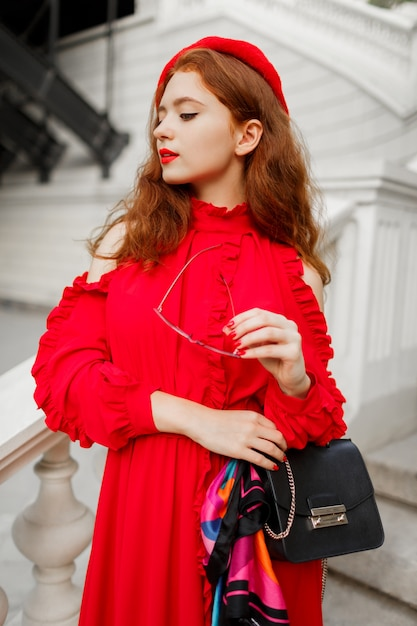 赤いベレー帽とエレガントなドレスを屋外でポーズでファッショナブルな生姜女性の肖像画。 無料写真