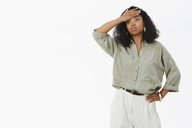 Портрет сытой, напряженной и измученной симпатичной темнокожей бизнесвумен в блузке и штанах, держащей руку на талии с выдохом Бесплатные Фотографии
