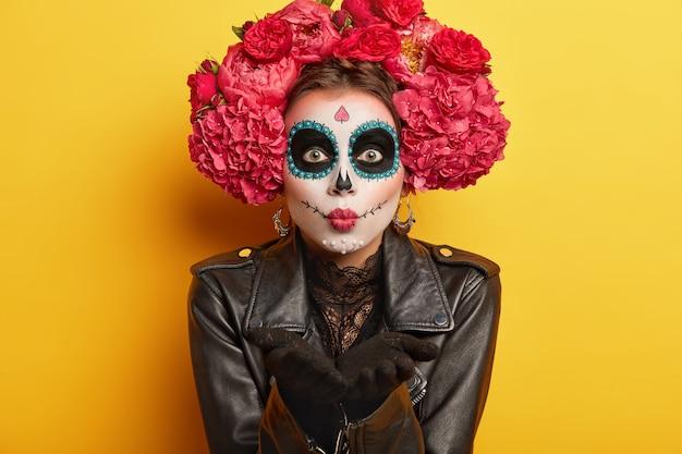 女性のダッパースケルトンの肖像画は、メキシコのカーニバルの準備をし、エアキスを吹き、頭蓋骨の化粧をし、黒いジャケットを着て、怖い顔をして、黄色の背景の上に孤立しています。ボディペイントとフェイスアート 無料写真