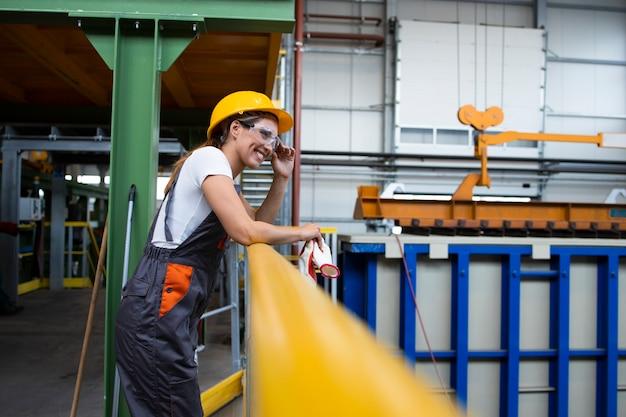 산업 생산 홀에서 금속 난간에 기대어 여성 공장 노동자의 초상화 무료 사진