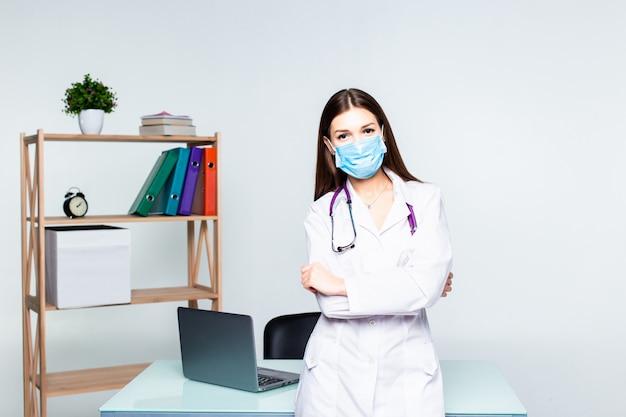 オフィスで聴診器を保持している彼女の胸に交差させた手で立っている女性医学療法士医師の肖像画。医療支援または保険の概念。 無料写真