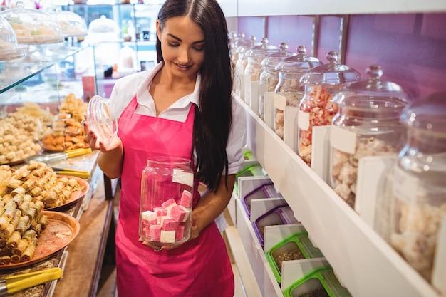 カウンターでトルコのお菓子の瓶を保持している女性の店主の肖像画 無料写真