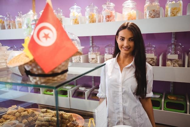 トルコのスイーツカウンターに立っている女性の店主の肖像画 無料写真