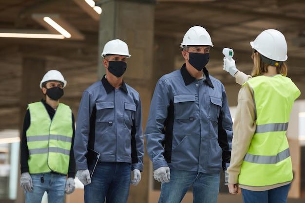 Портрет женщины-начальника, измеряющей температуру рабочих с помощью бесконтактного термометра на строительной площадке, меры безопасности от вируса короны Premium Фотографии