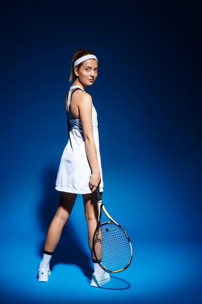 Портрет теннисистка с ракеткой позирует в студии Бесплатные Фотографии