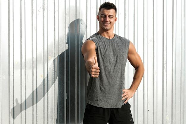 親指を上に向けるジェスチャーでフィットネスアスリートの男の肖像画。素敵な筋肉質の男。 無料写真