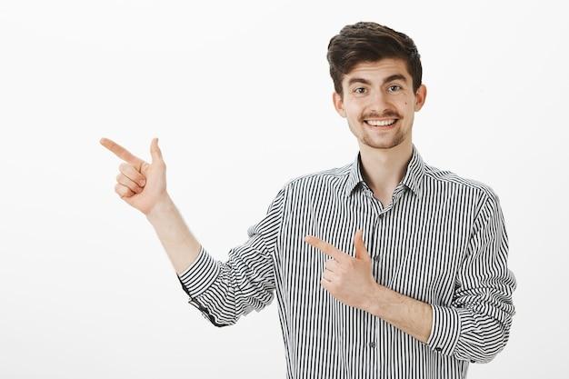 口ひげとあごひげのストライプのシャツで軽薄面白いヨーロッパの男性モデルの肖像画、指銃ジェスチャーで左を指し、広く笑って、かわいい女性にバーで話し続けることを勧め 無料写真
