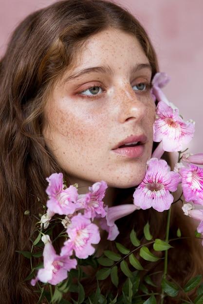 彼女の顔にピンクの花を持っているそばかすのある女性の肖像画 無料写真