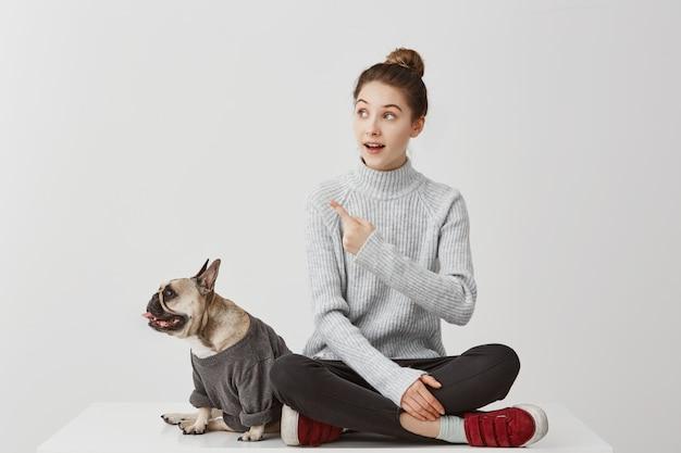 Портрет французского бульдога одел в фуфайке смотря в сторону на что-то пока милая девушка показывать. женский фотограф обращая внимание на любопытную вещь. люди, концепция животных Бесплатные Фотографии