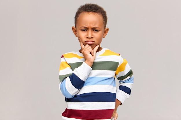 Портрет хмурого сварливого маленького темнокожего мальчика, выражающего нежелание или несогласие. серьезный африканский ребенок в стильном джемпере, держащий руку за подбородок, с расстроенным задумчивым взглядом Бесплатные Фотографии