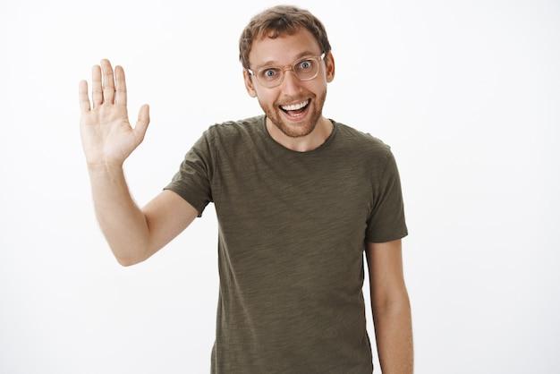 ダークグリーンのtシャツと手のひらを上げてこんにちはと言っている透明なガラスの面白い熱狂的な白人無精ひげを生やした男の肖像 無料写真