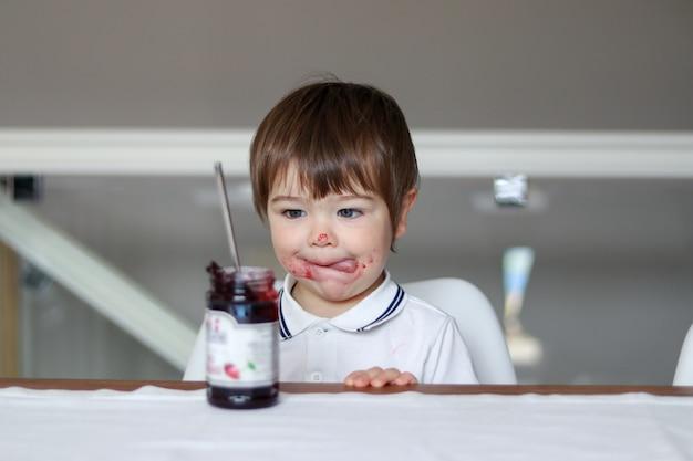 Портрет смешного маленького мальчика, глядя на стеклянную банку с вишневым вареньем с его языком и грязное лицо Premium Фотографии