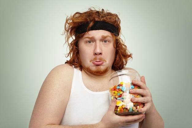 不幸で悲しい表情をした彼の頭の上のスポーツバンドと面白い太りすぎの若い赤毛の男性の肖像画 無料写真