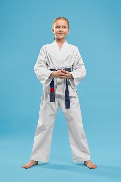 Портрет девушки в белом кимоно с голубым поясом в студии. Бесплатные Фотографии