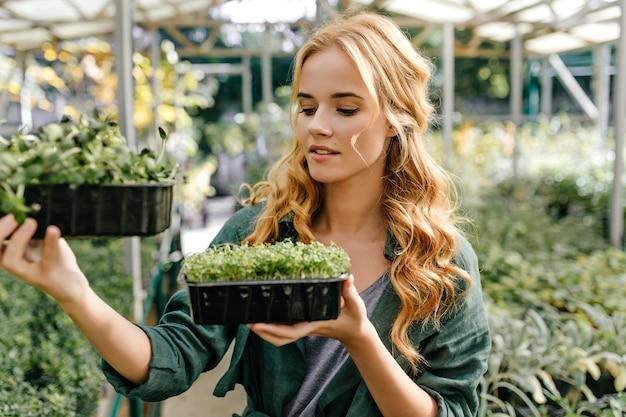 緑の小さな植物と2つのプラスチック製のポットを持って外の女の子の肖像画。若い女性の植物学者は緑を研究します。 無料写真