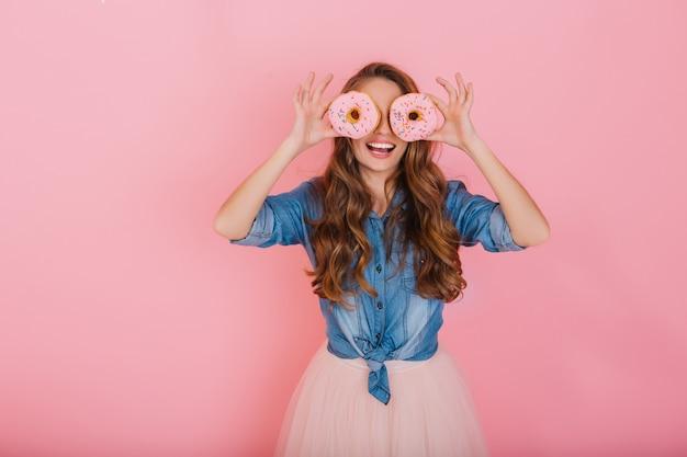 メガネとしてピンクのドーナツを押しながらバラ色の背景に分離されて笑っている長い髪の少女の肖像画。お茶を飲んだ後ドーナツを楽しんで愛らしい笑顔ブルネット若い女性 無料写真