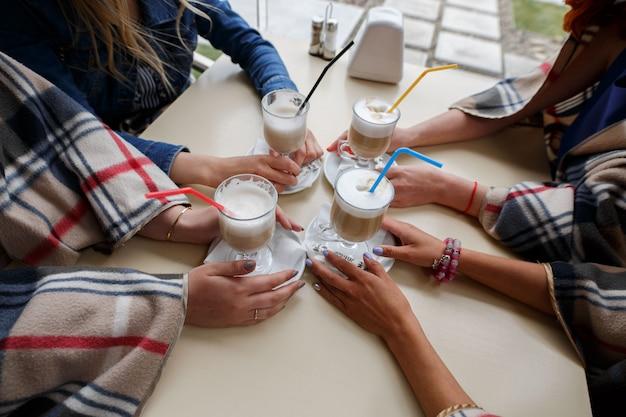 Портрет девушки пьют кофе в кафе крупным планом. стакан капучино с соломой в руках женщины. подружки говорят за чашкой кофе. подруги разговаривают и держат кофейные чашки в ресторане a Premium Фотографии