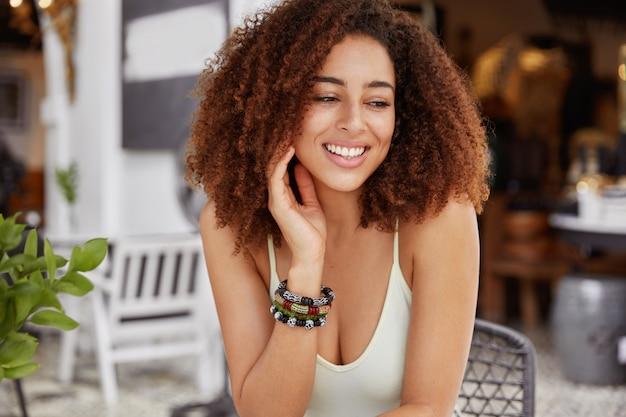 Портрет радостной афро-американской женщины с позитивной улыбкой, пышной прической смотрится с мечтательным выражением лица на фоне интерьера кафетерия. Бесплатные Фотографии