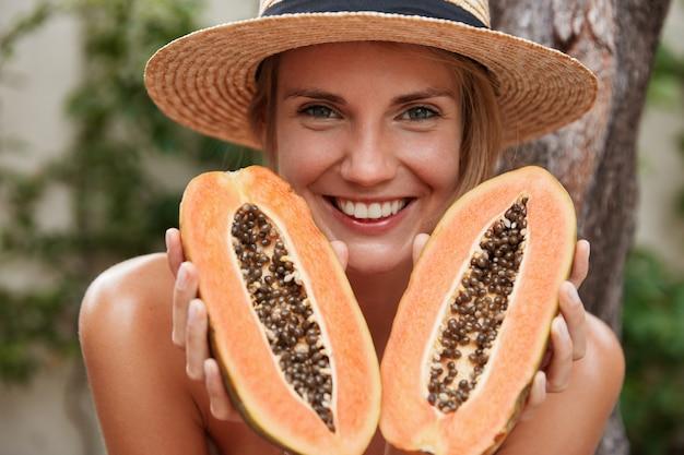 嬉しい素敵な女性の肖像画は裸のポーズ、夏の帽子をかぶって、エキゾチックな有機パパイヤを保持 無料写真