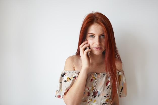 ピザの配達を注文し、電話で会話している長い生姜髪とそばかすを持つ魅力的なトレンディな見た目のかわいい女の子の肖像画。人、現代のライフスタイル、テクノロジー、コミュニケーションのコンセプト 無料写真