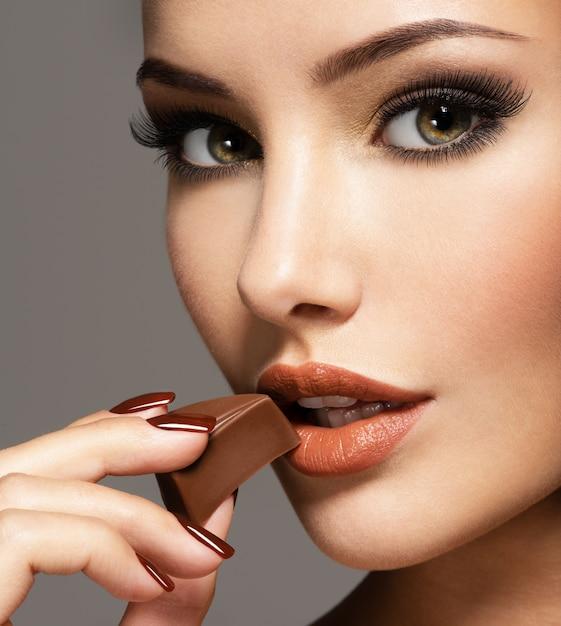 グラマーの肖像美女がチョコレート菓子を持って食べる。 無料写真