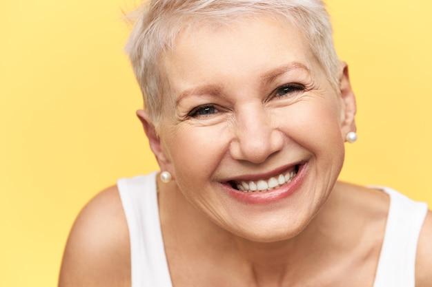Портрет симпатичной жизнерадостной европейской женщины средних лет со стильной прической в белой майке, выражающей положительные эмоции, широко улыбающейся, с прямыми зубами, радостной получать хорошие новости Бесплатные Фотографии