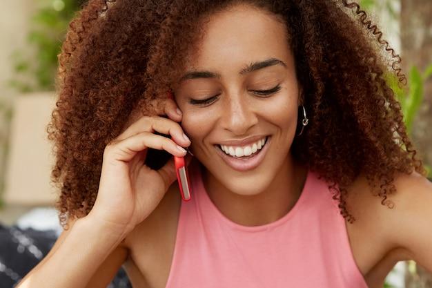 巻き毛の美しく暗い肌の女性の肖像画、前向きに見下ろし、親友との楽しい電話会話、海外での良い休暇の後の感想の共有 無料写真
