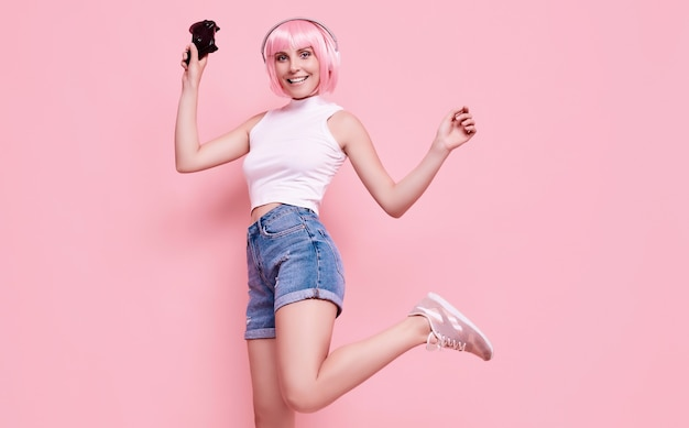 スタジオでカラフルなジョイスティックを使用してビデオゲームをプレイするピンクの髪のゴージャスな幸せなゲーマーの女の子の肖像画 無料写真
