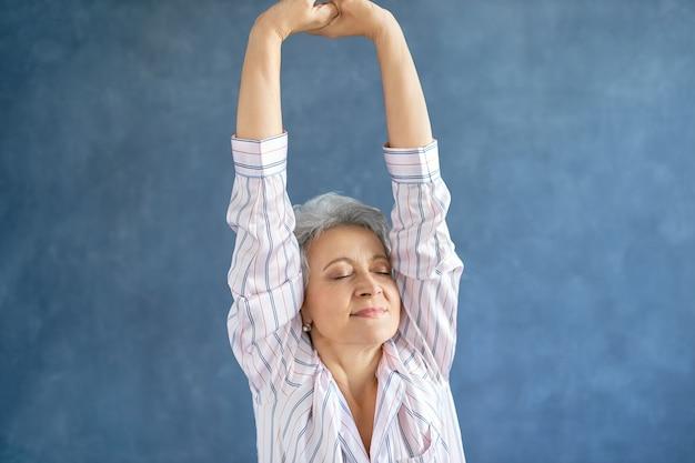 Портрет великолепной женщины средних лет в стильной полосатой пижаме, растягивающей тело после пробуждения рано утром Бесплатные Фотографии