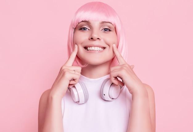 ピンクの髪のゴージャスな女性の肖像画は、ヘッドフォンで音楽を楽しんでいます 無料写真