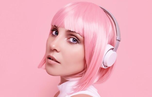 분홍색 머리를 가진 화려한 여자의 초상화는 헤드폰에서 음악을 즐긴다 무료 사진