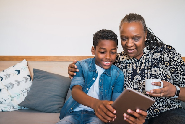 할머니와 손자 집에서 소파 소파에 앉아있는 동안 디지털 태블릿 셀카를 복용의 초상화. 가족 및 라이프 스타일 개념. 무료 사진