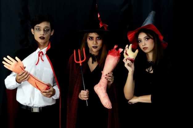 Портрет группы друзей азиатских молодых взрослых людей носить костюм хэллоуина, чтобы быть ведьмами и персонажем дракулы. празднование хэллоуина и концепция международного праздника. Premium Фотографии