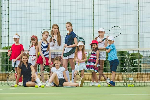 Портрет группы в составе девушки и мальчик как теннисисты держа ракетки тенниса против зеленой травы открытого суда. Бесплатные Фотографии