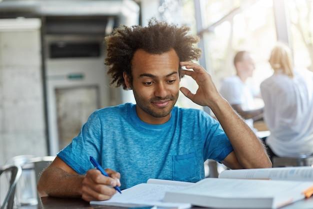 과학 연구 또는 프로젝트를 준비하는 뭔가를 모르고 그의 머리를 긁적 메모를 작성하는 대학 매점에서 책상에 앉아 덥수룩 한 머리를 가진 잘 생긴 아프리카 계 미국인 남성의 초상화 무료 사진