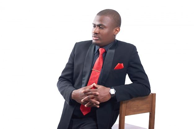 エレガントな黒のスイートと椅子にもたれて赤いネクタイを身に着けているハンサムなアフリカビジネスの男性の肖像画 無料写真