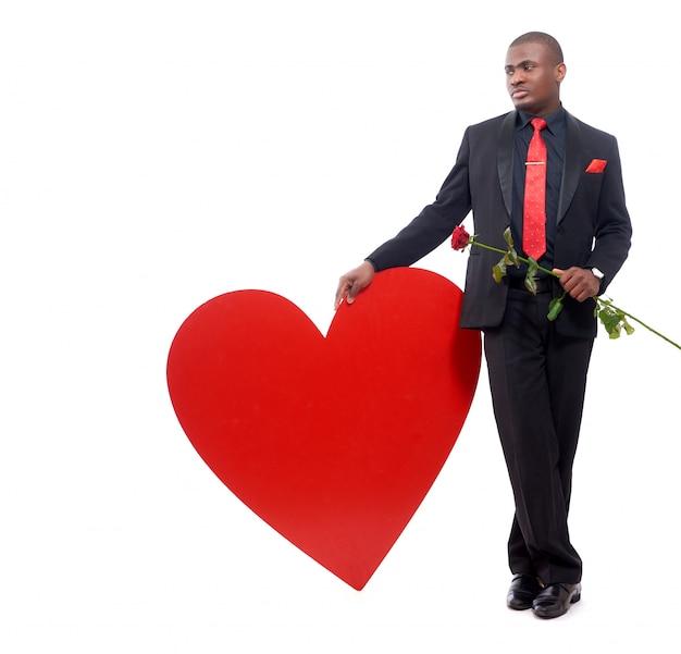 Портрет красивого африканского человека, опирающегося на большое украшенное красное сердце и держащего красную розу Бесплатные Фотографии