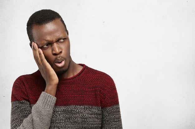 Портрет красивый афро-американских мужчин студент или клиент хмурится, глядя в сторону с шокирован или озадачен выражением, держа руку на лице. темнокожий мужчина с зубной болью, касаясь щеки Бесплатные Фотографии