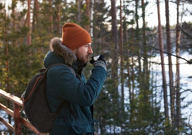 도보로 숲 여행에서 야외 뜨거운 차를 마시는 잘 생긴 수염 난된 남자의 초상화 무료 사진