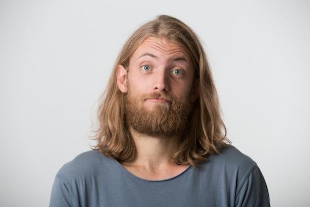 Портрет красивого бородатого молодого человека со светлыми длинными волосами в серой футболке выглядит серьезным и уверенным, изолированным на белой стене Бесплатные Фотографии