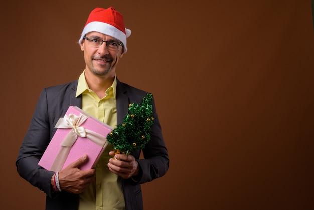 브라운에 크리스마스를위한 준비 잘 생긴 사업가의 초상화 프리미엄 사진