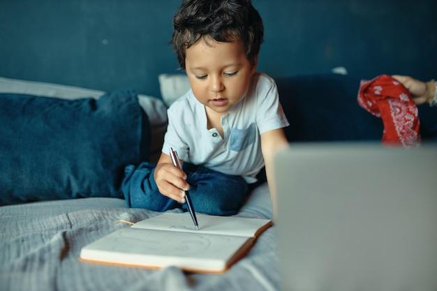Портрет красивого сконцентрированного маленького мальчика смешанной расы, сидящего на кровати с блокнотом и карандашом, рисующего, сфокусировав выражение лица Бесплатные Фотографии