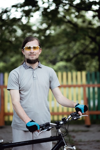 컬러 울타리에 따뜻한 여름 저녁에 야외에서 서 잘 생긴 자전거 타는 사람의 초상화 프리미엄 사진
