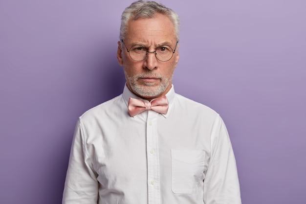 Портрет красивого седого европейца выглядит со строгим выражением лица через круглые очки, носит строгую белую рубашку и галстук-бабочку. Бесплатные Фотографии
