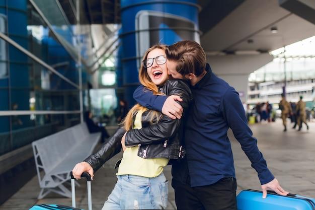 空港で外の長い髪を持つ少女をキス黒いシャツのひげを持つハンサムな男の肖像画。彼女はメガネ、黄色いセーター、ジーンズのジャケットを着ています。彼女は幸せそうです。 無料写真