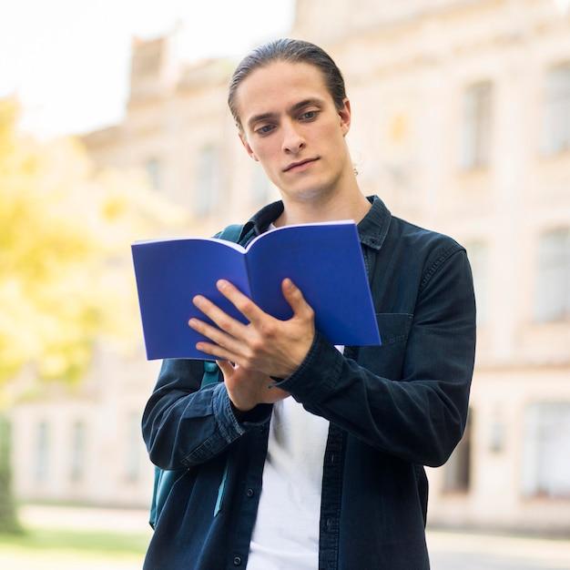 キャンパスで勉強しているハンサムな男性の肖像画 無料写真