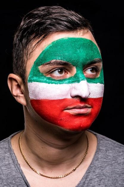 Портрет болельщика сторонника лица красивого человека сборной ирана с раскрашенным лицом флага, изолированным на черном фоне. поклонники эмоций. Бесплатные Фотографии