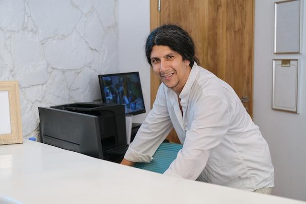 리조트 호텔의 리셉션 데스크에서 일하는 잘 생긴 남자의 초상화 프리미엄 사진