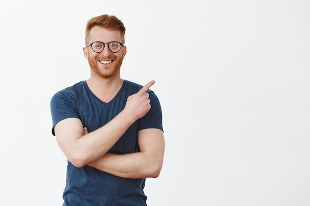 Портрет красивого рыжего мужчины с щетиной в очках и футболке, указывающего на верхний правый угол и радостно улыбающегося Бесплатные Фотографии
