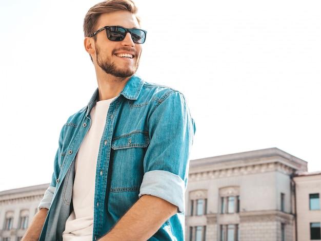 Портрет красивый улыбающийся стильный битник lumbersexual бизнесмен модель. человек, одетый в джинсовую куртку одежды. Бесплатные Фотографии